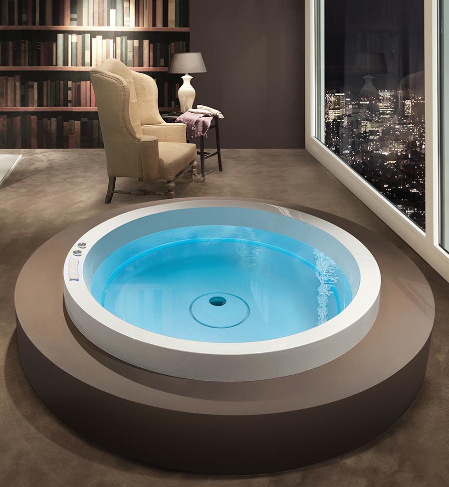 Luxusní kulatá vířivka s čistým designem umístěná v interiéru.