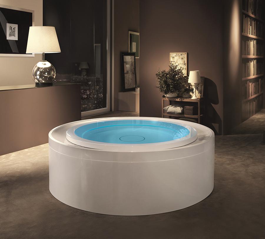 Luxusní designová kulatá volně stojící vířivka s přelivnou hranou, umístěná v interiéru.