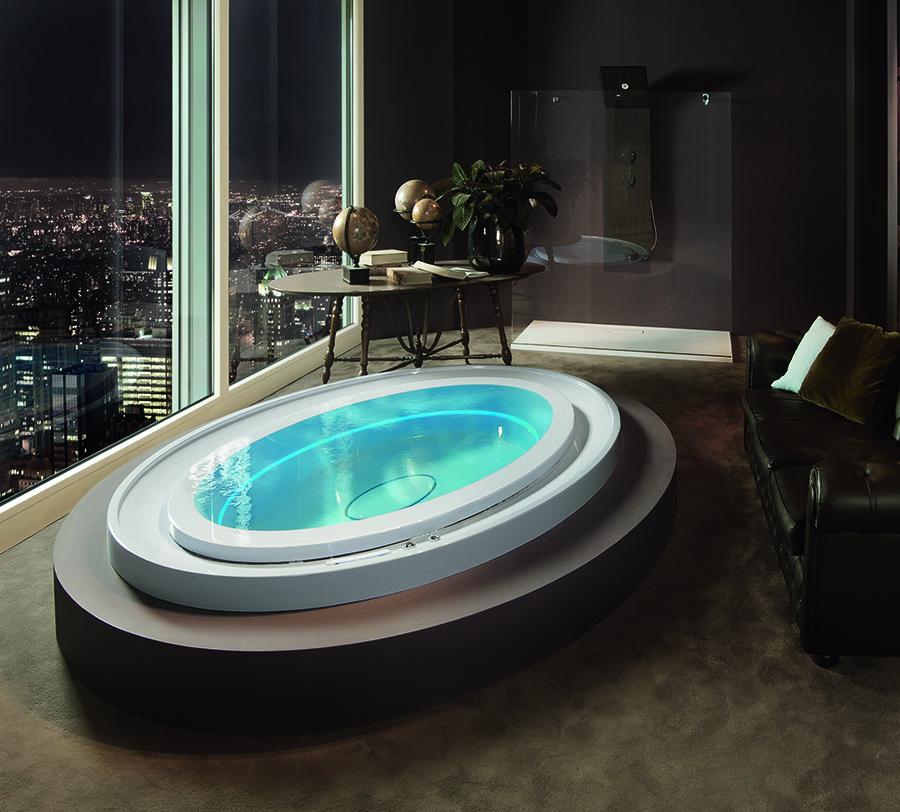 Luxusní designová oválná vířivka s přelivnou hranou umístěná v interiéru.